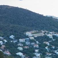 Ο δασώδης λόφος τής Σαρωνίδας, με τα σπίτια στις πλαγιές του